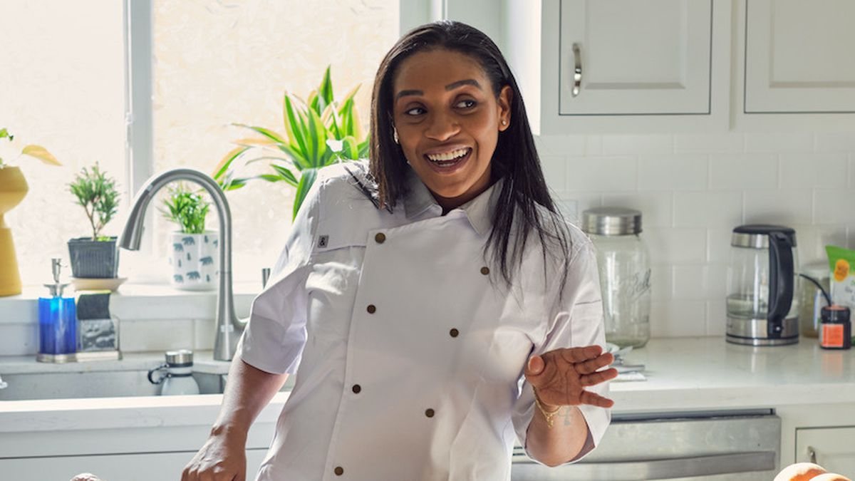 A woman with long black hair points at the camera in her chef's coat