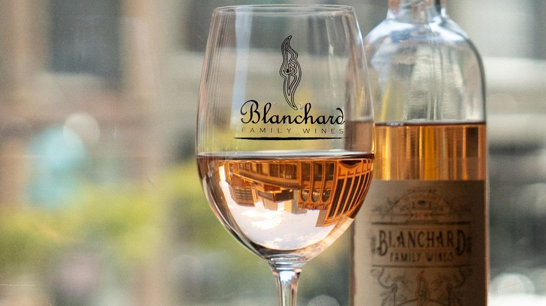 A close-up photo of a glass and bottle of white wine from Blanchard Family Wines