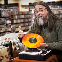 """Chris Bown poses Thursday, April 19, 2012, in Scarborough, Maine, with a copy of The Knack's """"Live in Los Angeles 1978."""" The vinyl record is being released for Record Store Day on Saturday, April 21. Brown, the head of marketing for Bull Moose Music, conceived of the day five years ago. This year there'll be more than 300 new and special releases."""