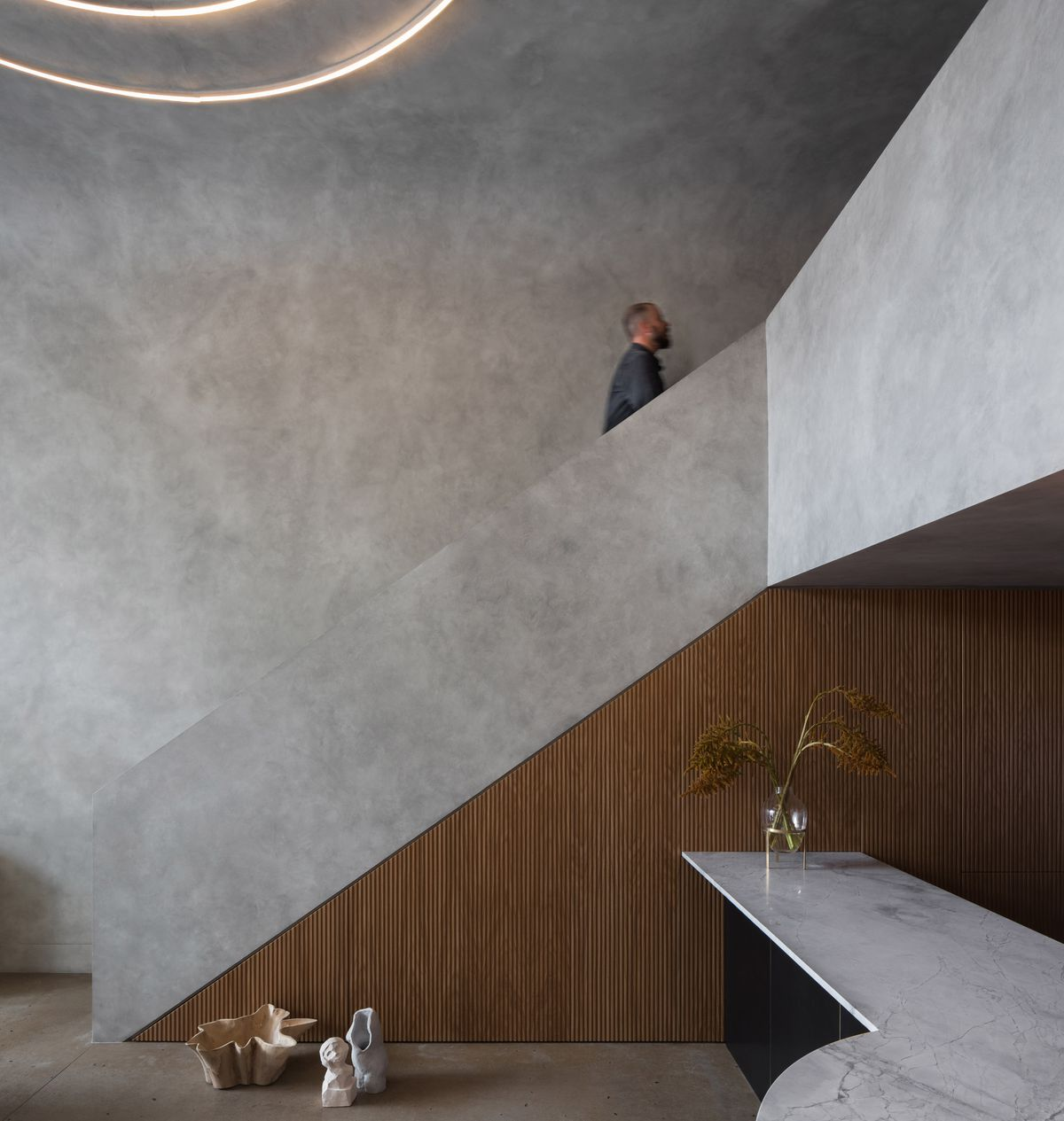 A man walks up a staircase that has a concrete bannister. There are concrete walls and concrete ceilings.