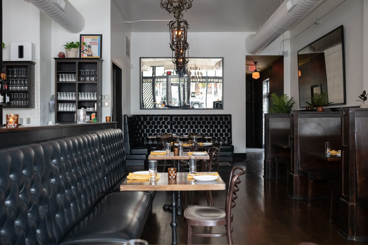 A view straight on of the dining room with black tufted booths, wooden chairs, and blonde table tops.