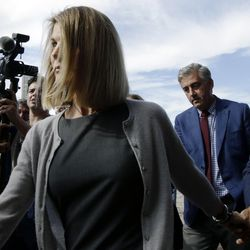 Lori Loughlin departs federal court Tuesday, Aug. 27, 2019, in Boston, after a hearing in a nationwide college admissions bribery scandal. At far right is her husband, clothing designer Mossimo Giannulli.