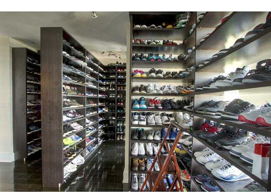 A closet with so many shoes from floor to ceiling on many custom shelves.
