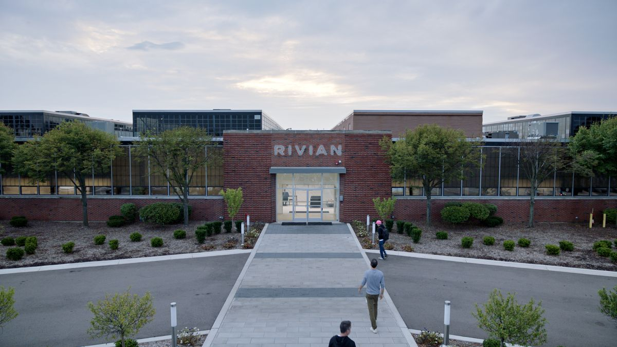 A brick facade with Rivian in block letters over the entrance. There's slightly taller glass buildings behind.