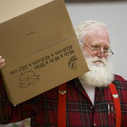 Volunteer Merlin Taylor carries a box of donations as the 19th annual Candy Cane Corner holiday store prepares to open in the old Granite High School pool building in South Salt Lake on Monday, Nov. 30, 2015.
