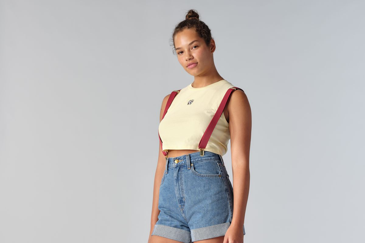 A model wears Levi's denim shorts, yellow crop top, and red suspenders, evoking Pokémon trainer Misty