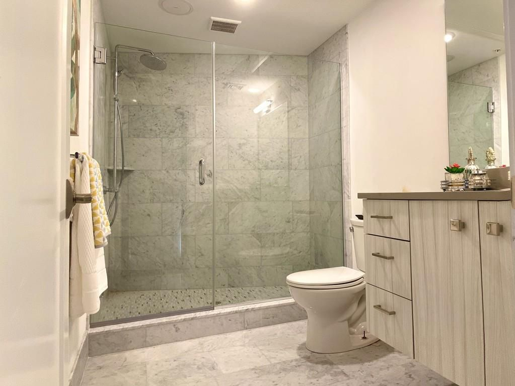 A bathroom with a glass-enclosed shower taking up one end.