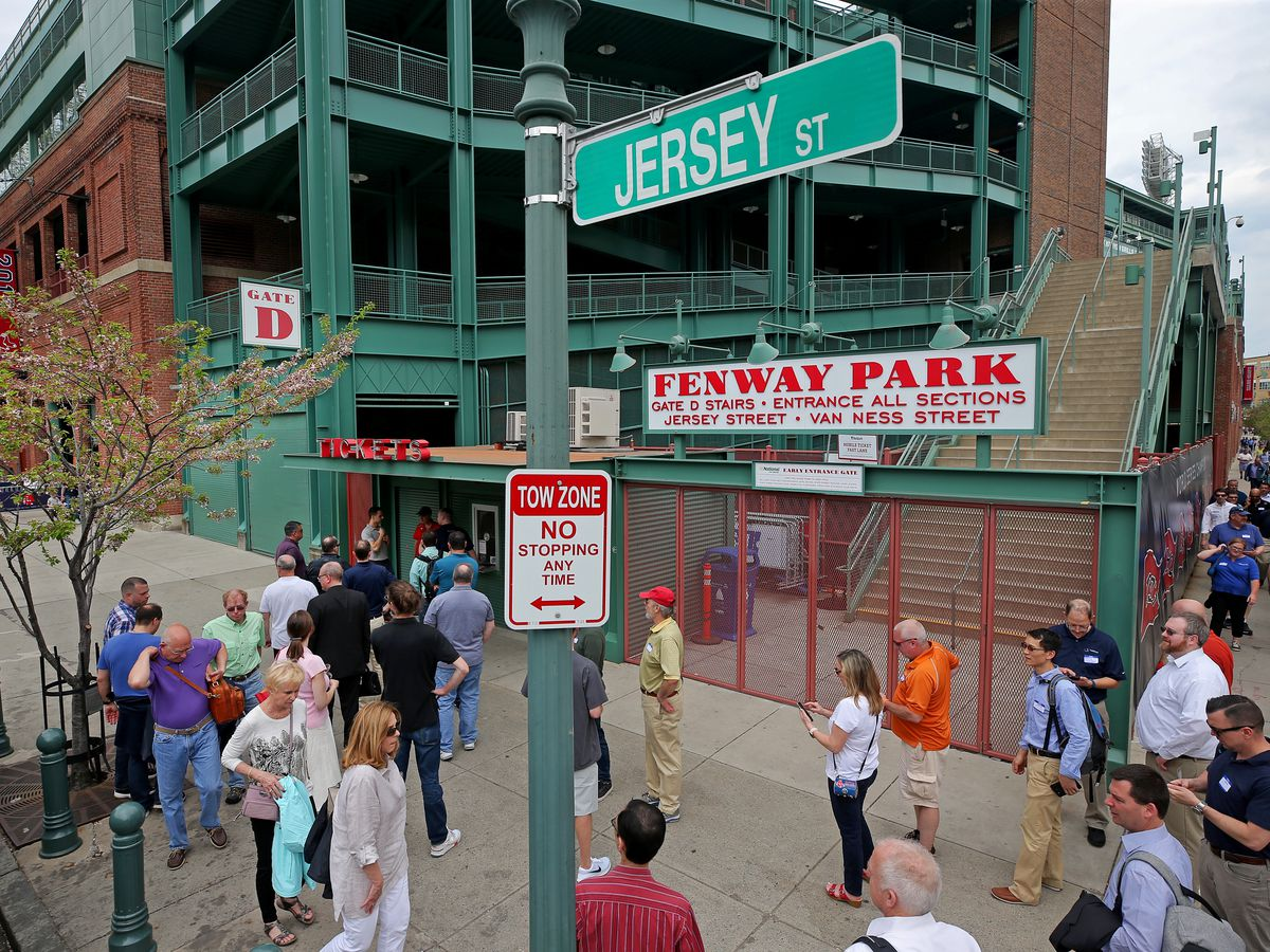 People milling about next to a ballpark.