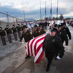 Unified police officer Doug Barney's casket is carried into the the Maverik Center in West Valley City on Monday, Jan. 25, 2016, prior to his funeral.
