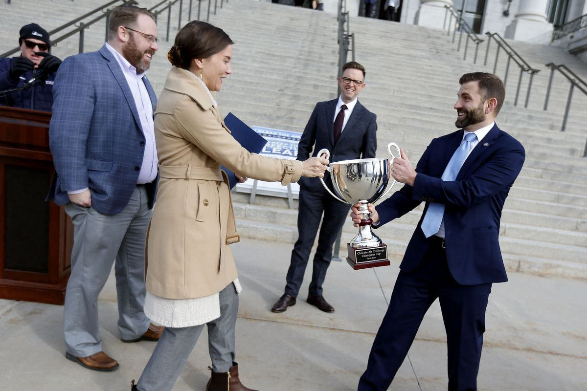 Salt Lake City Mayor Erin Mendenhall and Scott Baird, executive director of the Utah Department of Environmental Quality, jokingly fight over a trophy before the kickoff of the 11th annual Clear the Air Challenge at the Capitol in Salt Lake City on Friday, Jan. 31, 2020. The Utah Department of Environmental Quality won the challenge in 2019. Baird said DEQ employees won last year by increasing their use of public transportation and inviting food trucks to their office location so that employees did not have to go out for lunch.