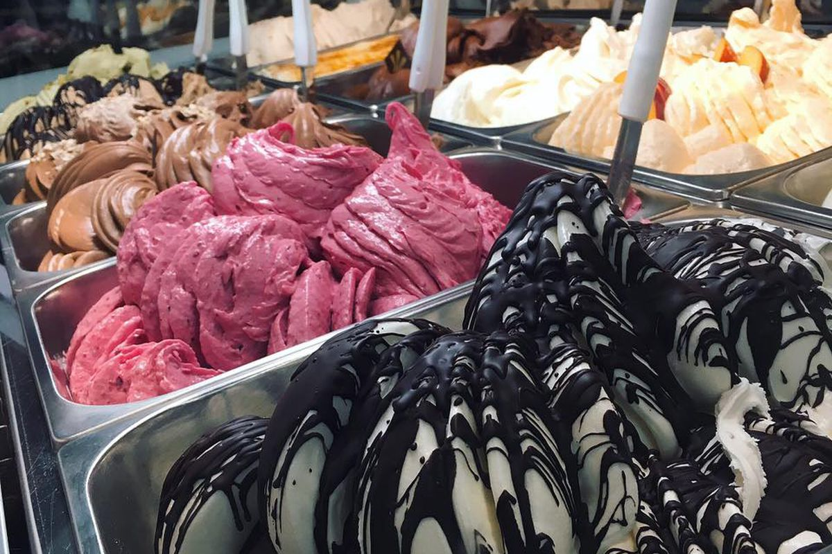 10 colorful flavors of gelato are visible in a gelato shop display, each in a metal bin with a spoon sticking out of it