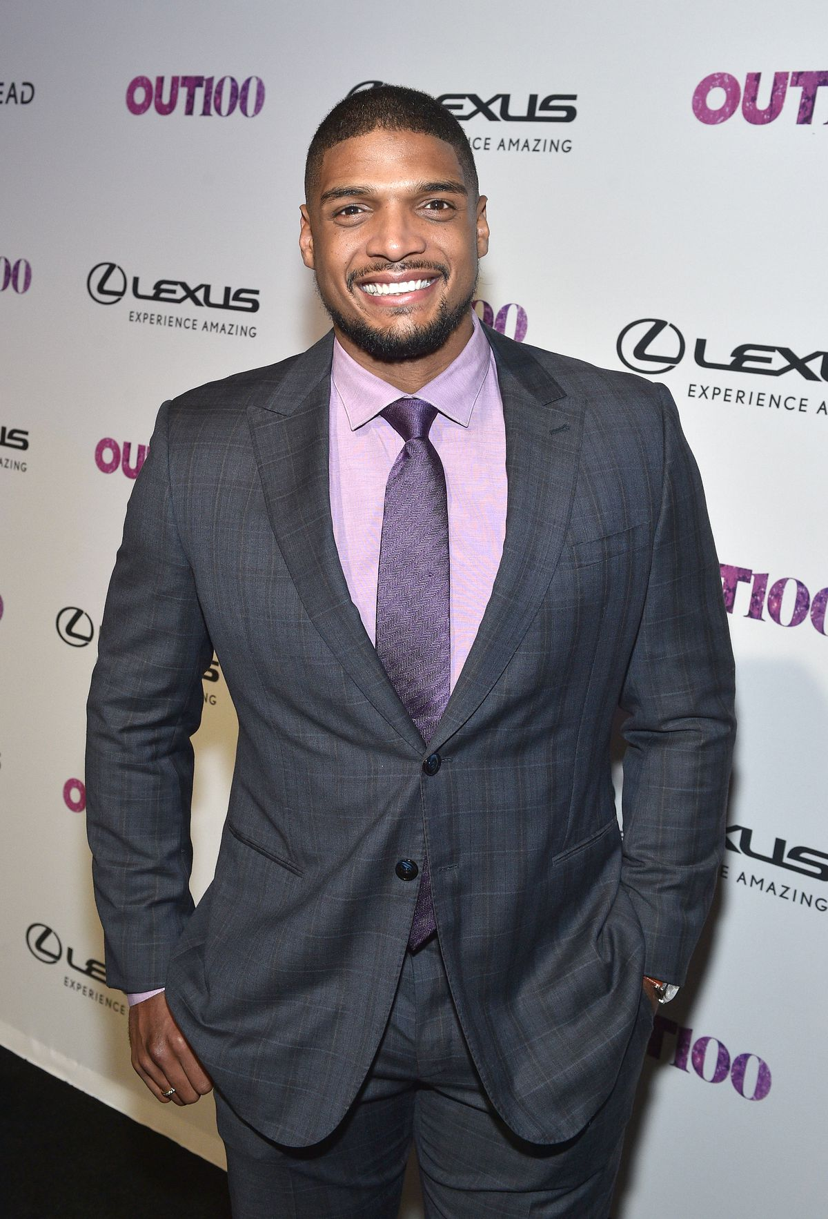 Michael Sam dressed in a suit and tie appears at an Out Magazine event.