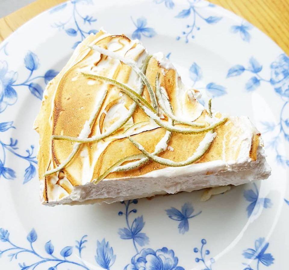 Overhead view of a slice of pie with a thick layer of toasted meringue and candied lime on a white plate patterned with delicate blue flowers