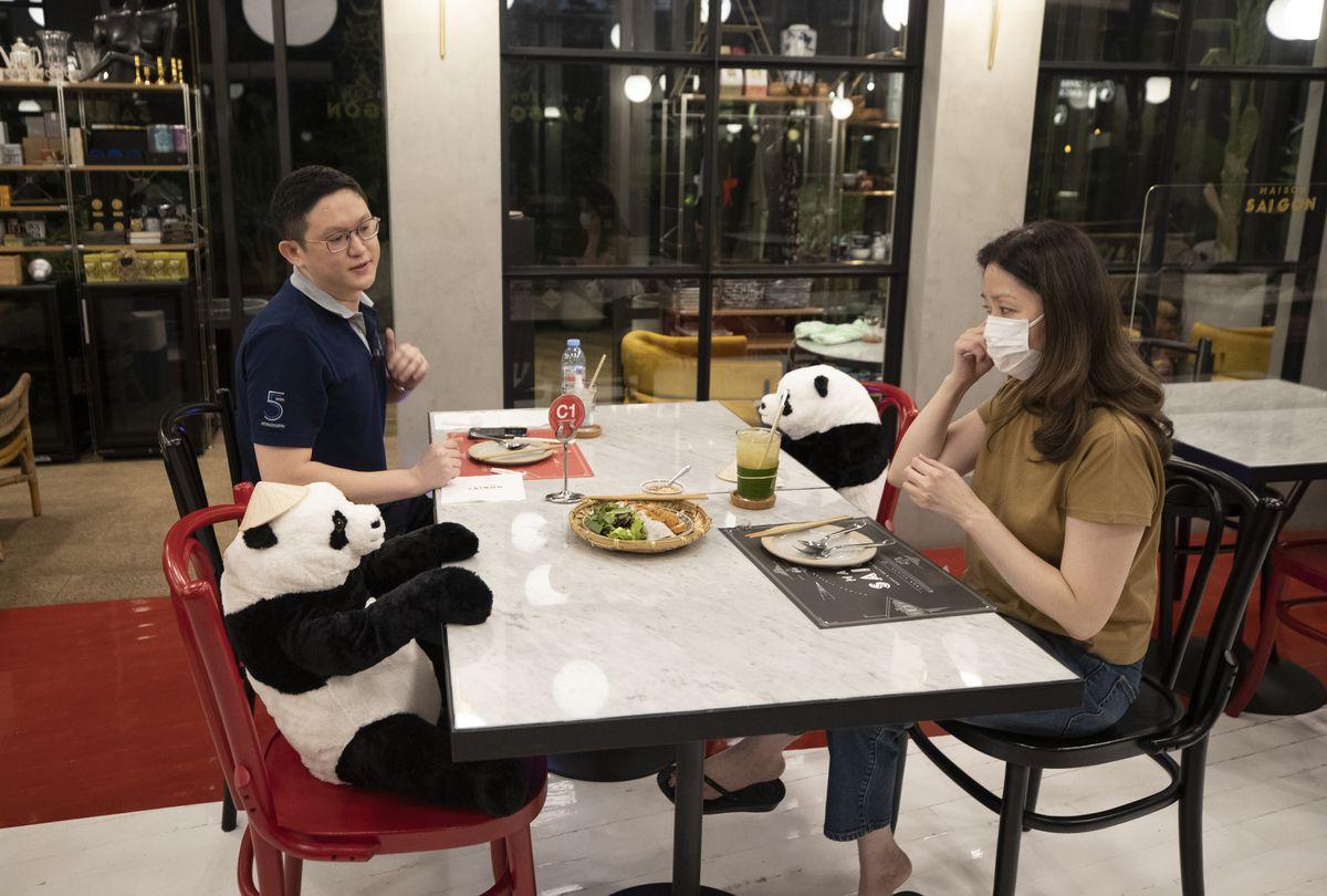 Customers of the Maison Saigon restaurant sit next to stuffed panda dolls.