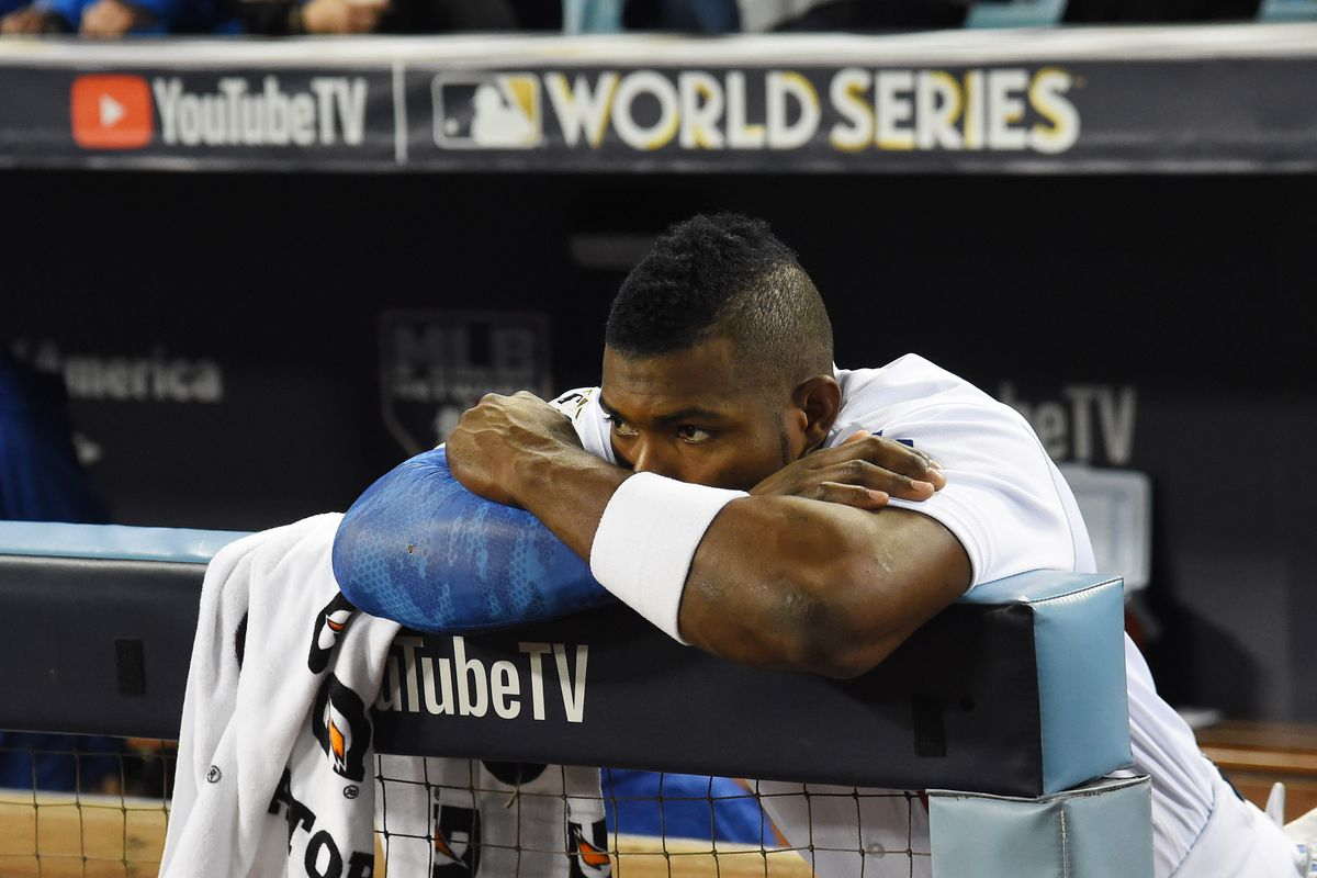Los Angeles Dodgers right fielder Yasiel Puig stands in the dugout, looking disappointed