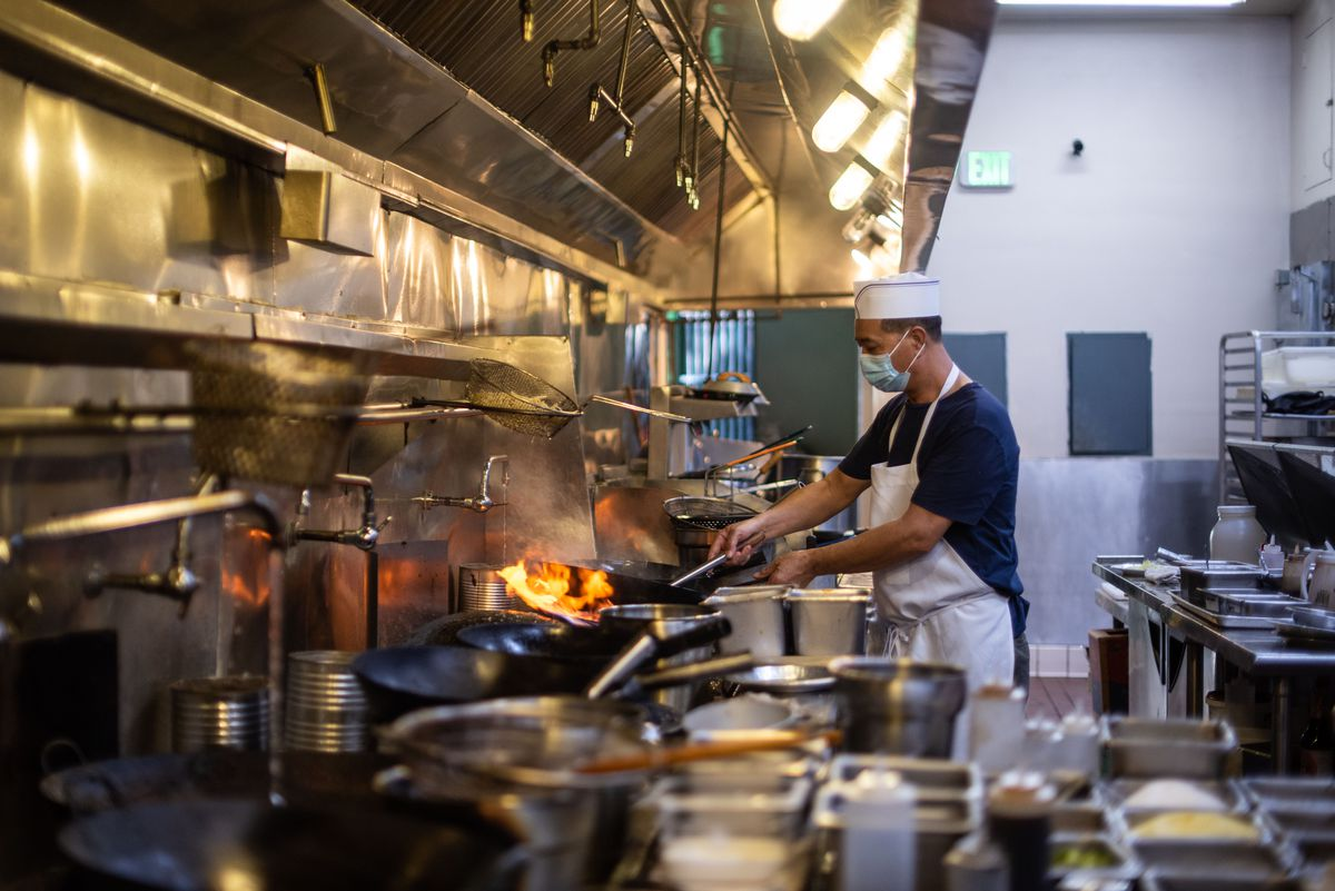 A chef cooks with a hot wok in the kitchen of a Chinese restaurant.