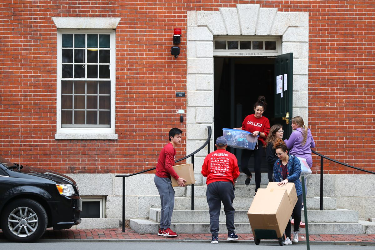Harvard students carry boxes as they move out of their dorm rooms on March 12.