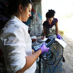Calah Worthen, left, environmental scientist for the Utah Department of Environmental Quality's water quality division, reads water quality measurements at the Jordan River in Salt Lake City on Monday, July 18, 2016, as environmental scientist Suzan Tahir records the measurements.