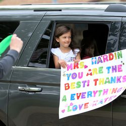 A teacher at Farr West Elementary in Farr West, Weber County, waves a scarf at a student and parent holding a sign during a drive-by parade in front of the school on the last day of classes on Friday, May 15, 2020.