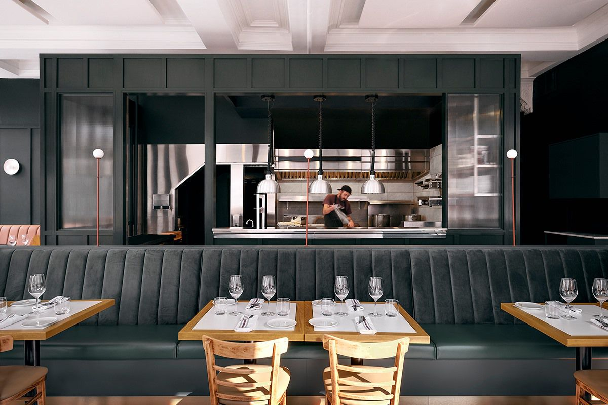 grey banquettes in restaurant with cook behind