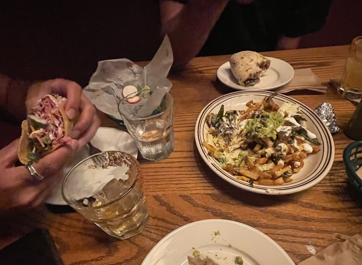 A table full of dishes, including tacos, burritos, and french fries topped with cheese and crema