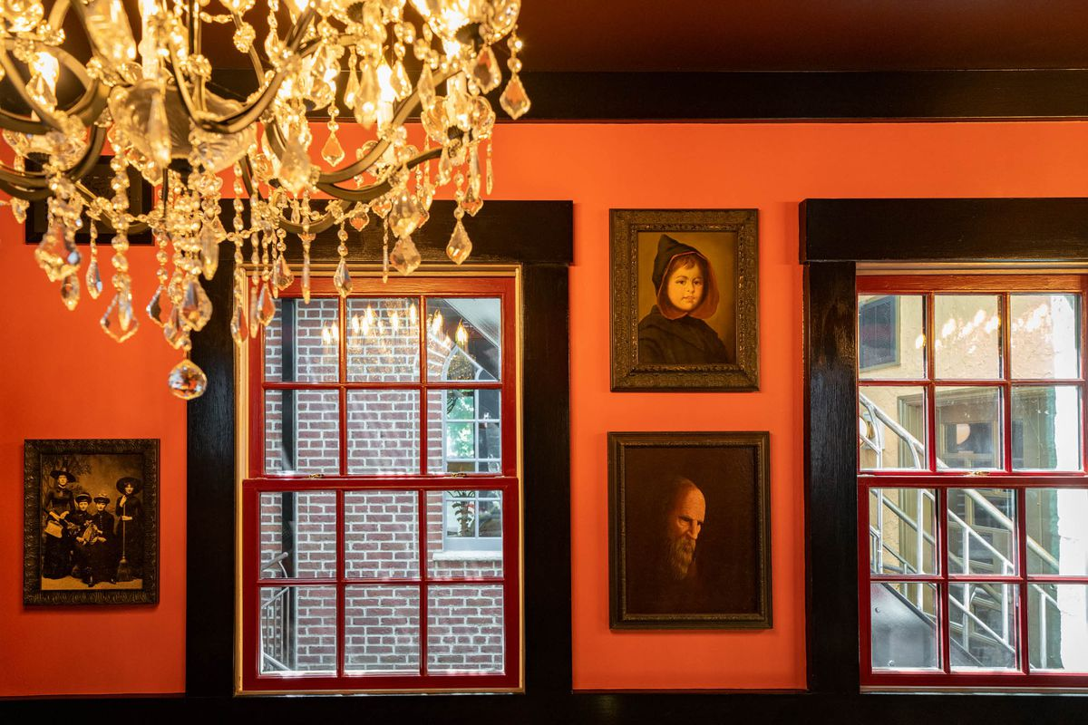 A series of three creepy, dark portraits of various people dressed in 19th-century garb are hung on a dark maroon wall with a crystal hanging from the ceiling.