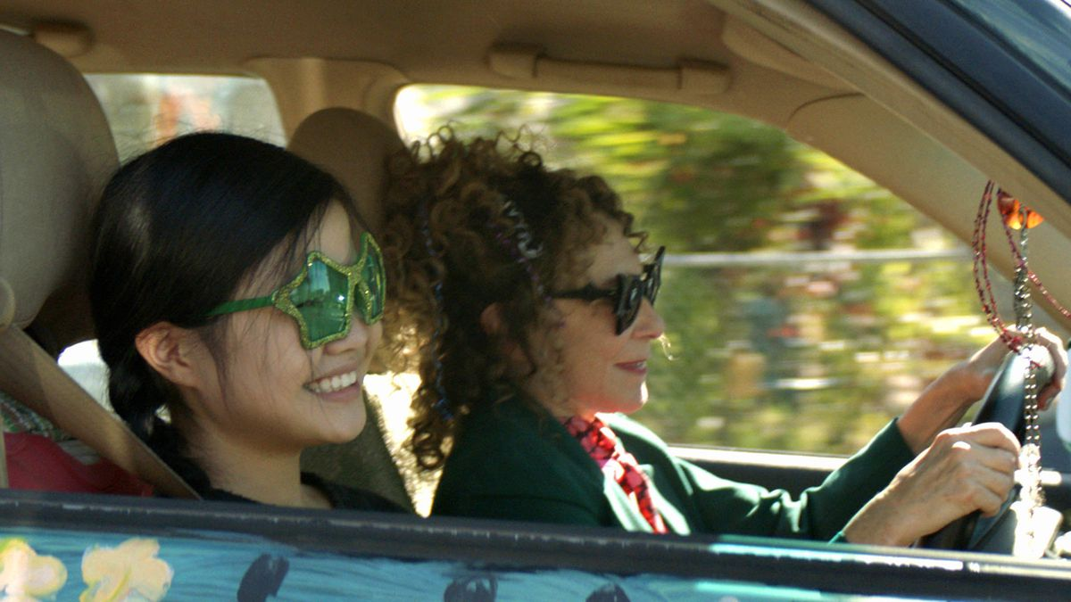 A teenaged girl and an older woman drive in a car wearing novelty sunglasses and smiling.