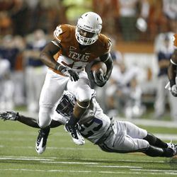 Running back Malcolm Brown #28 of the Texas Longhorns gets past defensive back Skye PoVey #29 of the BYU Cougars on September 10, 2011 at Darrell K. Royal-Texas Memorial Stadium in Austin, Texas.  Texas defeated BYU 17-16.  (Photo by Erich Schlegel/Getty Images)