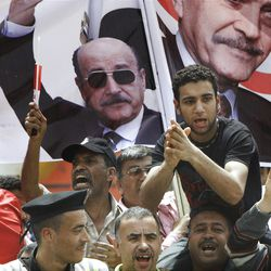 Supporters of former Egyptian Vice President Omar Suleiman chant in front of his posters out side the Higher Presidential Elections Commission, in Cairo, Egypt, Sunday, April 8, 2012. A former strongman of ousted President Hosni Mubarak's regime has announced his presidential candidacy, shaking up an already heated race that is emerging as a contest between two longtime rivals _ former regime officials and Islamists who have surged in influence. (AP Photo/Amr Nabil)