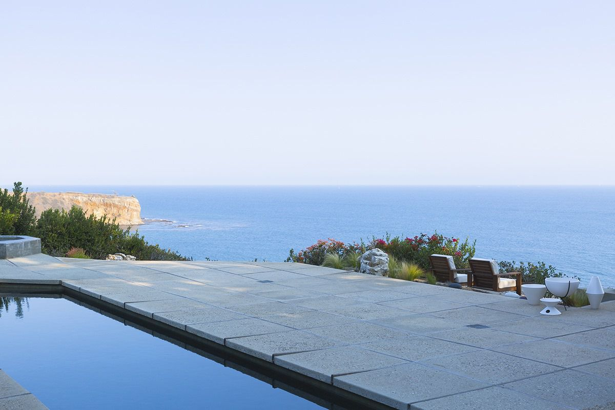 A pool and a concrete deck overlooking the ocean on a sunny day.