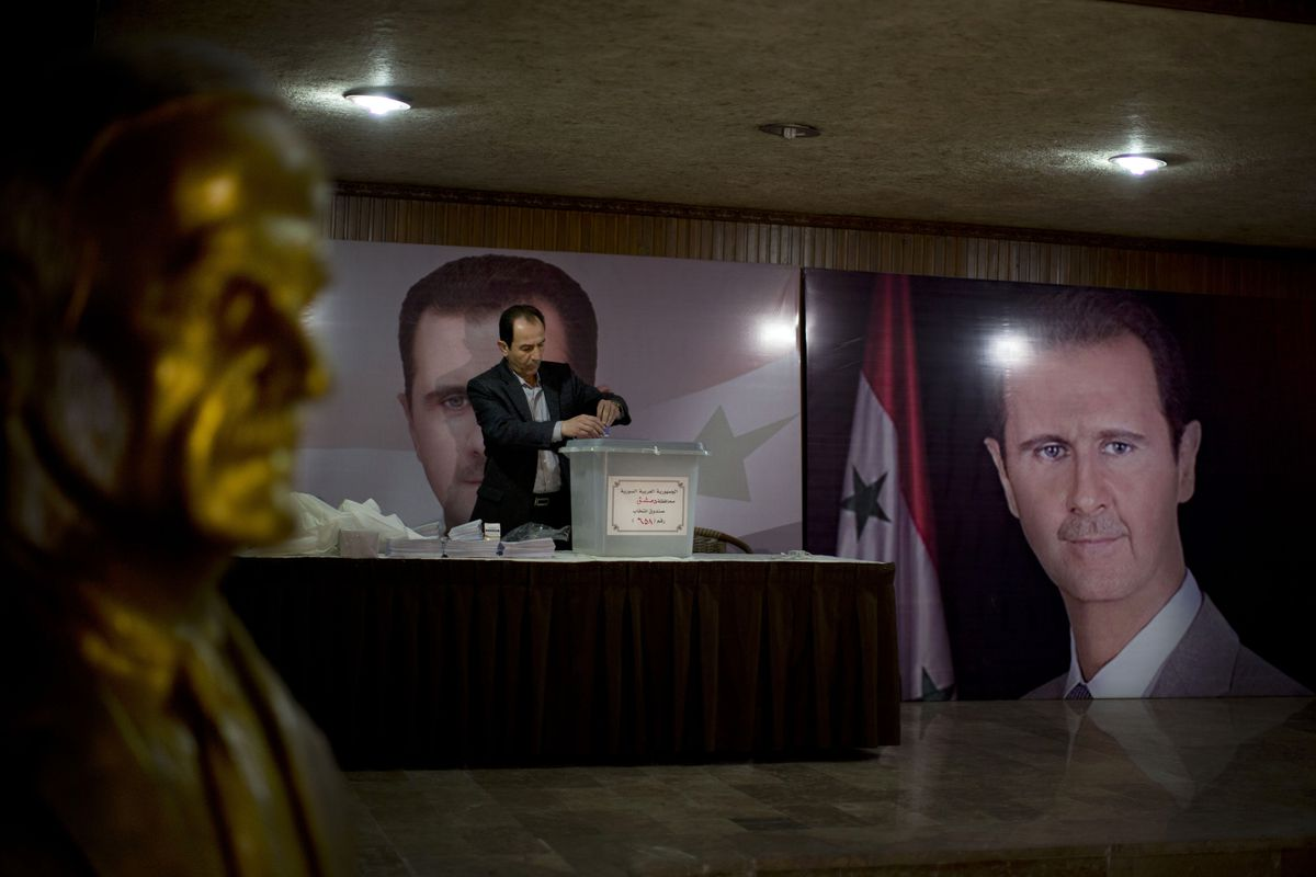 In this April 13, 2016 file photo, a Syrian election official waits for voters at a polling station with posters of President Bashar Assad during the parliamentary election in Damascus, Syria.