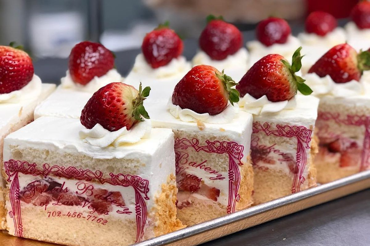 A tray of Freed's Bakery's famous wedding cake dessert slice topped with California strawberries.