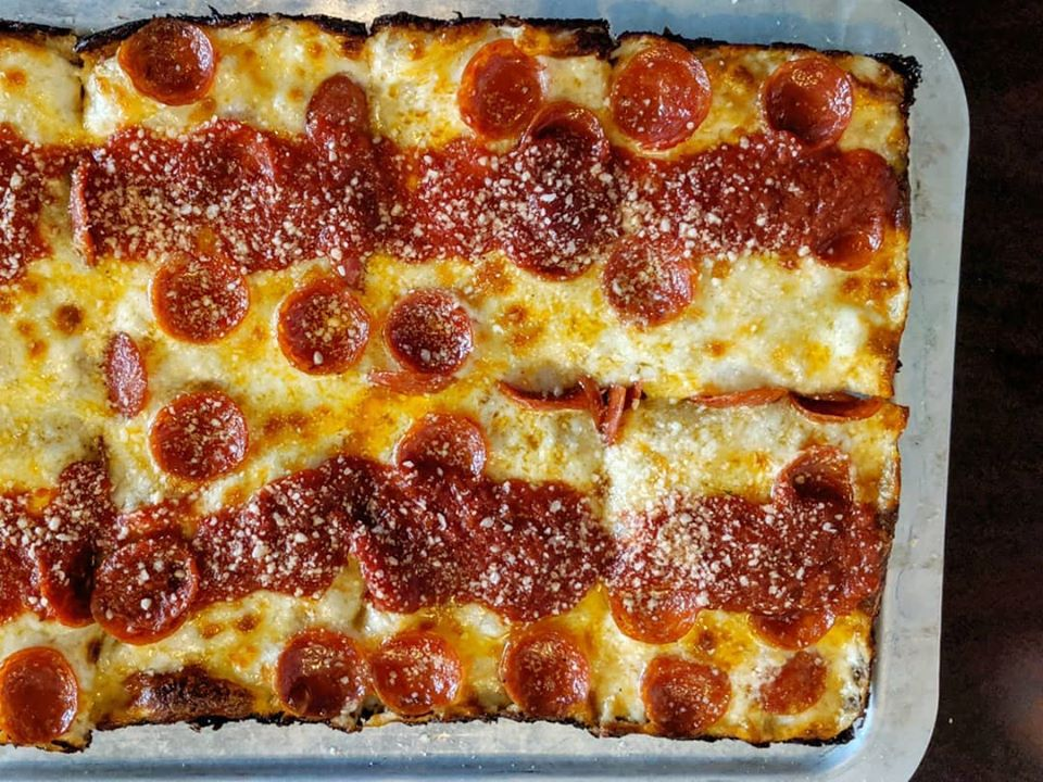 Overhead view of a rectangular pepperoni pizza, with two horizontal strips of tomato sauce across