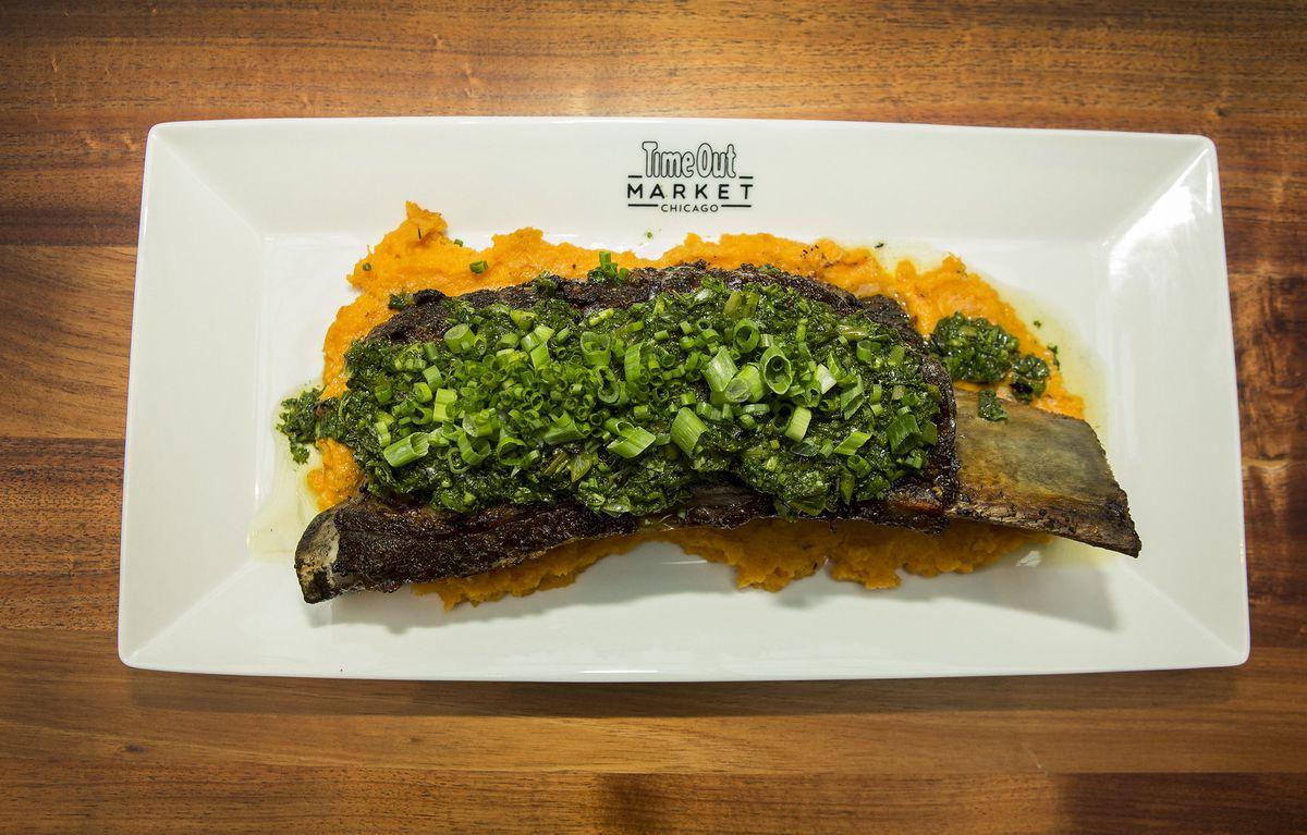 A large beef rib on the bone with charred salsa verde and horseradish sweet potatoes.
