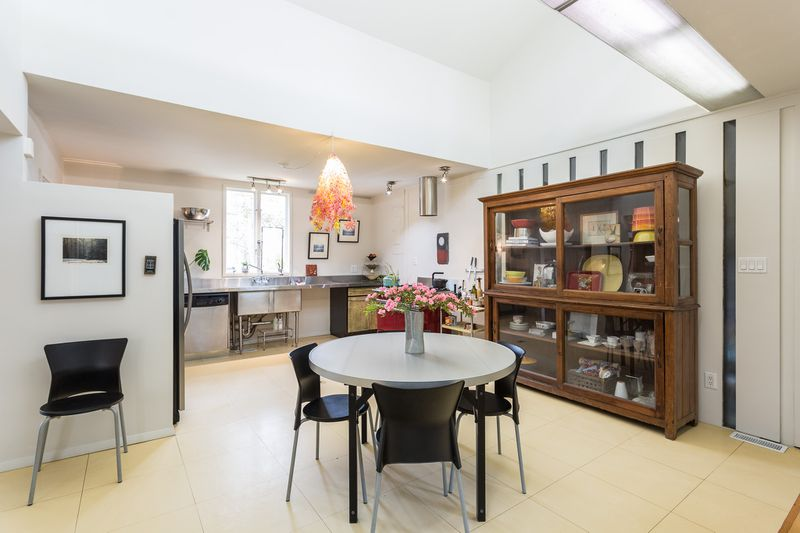 A kitchen has skylights above, a four-person eat-in area, and a large wooden cabinet for plates.