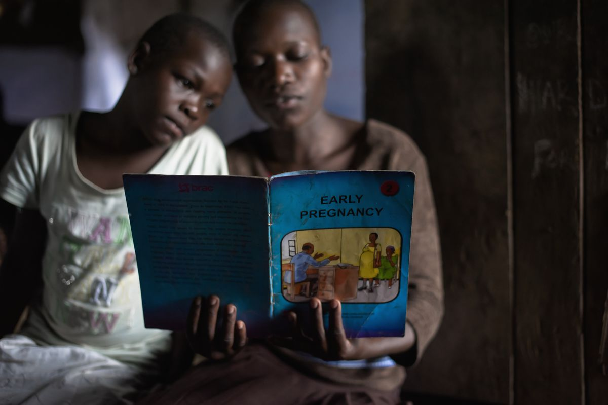 Girls read an educational book at an adolescent youth center in Uganda. Low contraceptive usage has fueled fertility, with 59 percent of girls in Uganda pregnant by the age of 20.