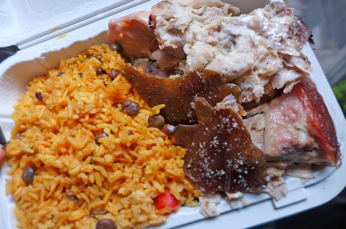 Pork roast with skin glisten with fat, with yellow rice and pigeon peas on the side in a carryout container.