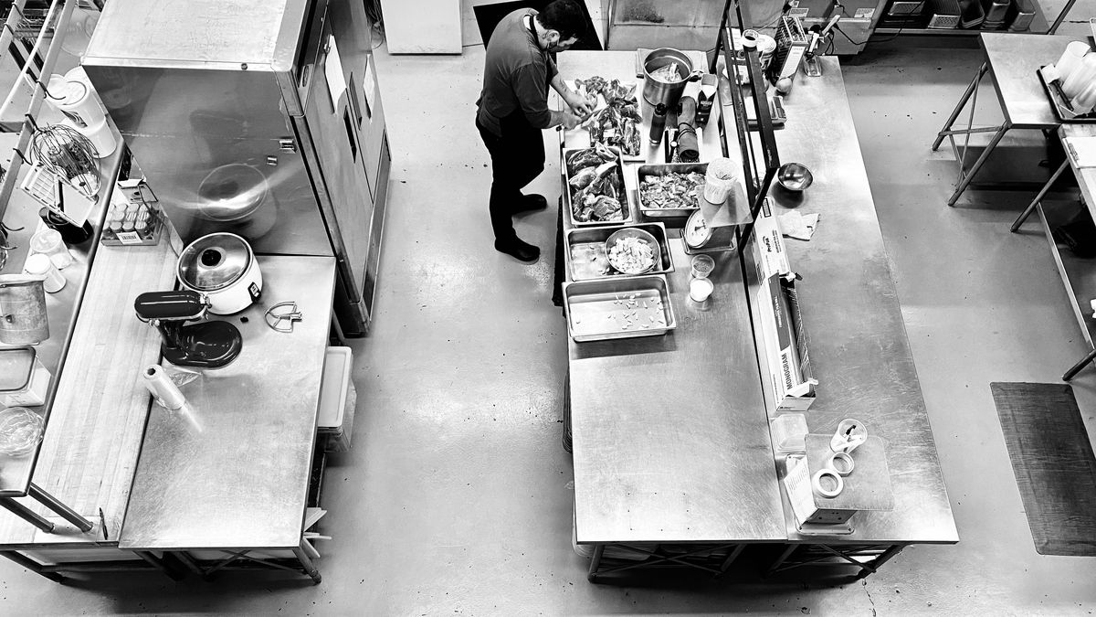 A man stands in the kitchen at Chefstable preparing dishes