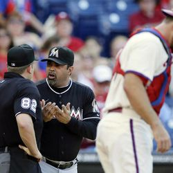 Miami Marlins manager Ozzie Guillen, center, discusses a call with home plate umpire Clint Fagan, left, in the second inning of a baseball game against the Philadelphia Phillies, Wednesday, Sept. 12, 2012, in Philadelphia. At right is Philadelphia catcher Erik Kratz.