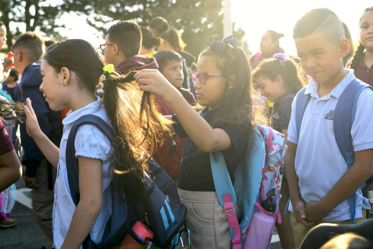 An elementary-age girl braids the hair of another girl as they stand amid a group of students wearing backpacks in 2018.