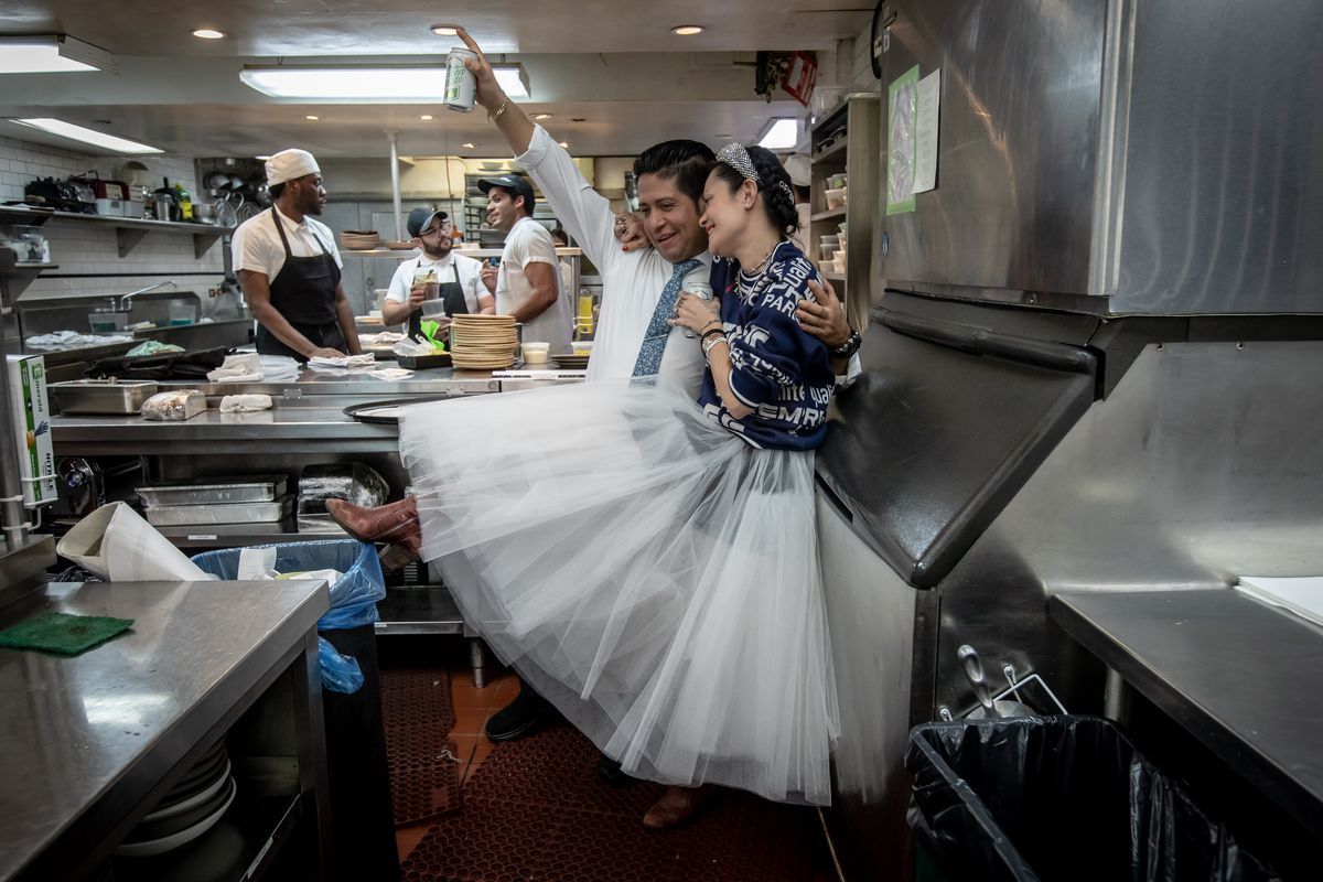 Regular customer Bianca Jebbia, wife of Supreme founder James Jebbia, wears a large white tutu while saying goodbye to the kitchen staff