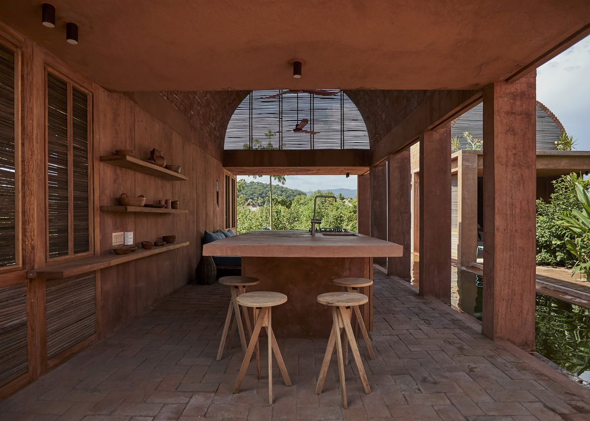 A closer look at the open-air kitchen with a large island and wooden barstools clustered underneath. The shelves on the left wall hold ceramic mugs.