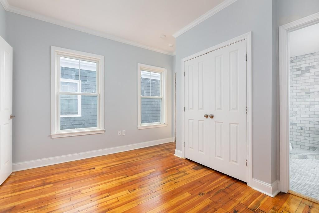 An empty bedroom with windows and a closed closet.