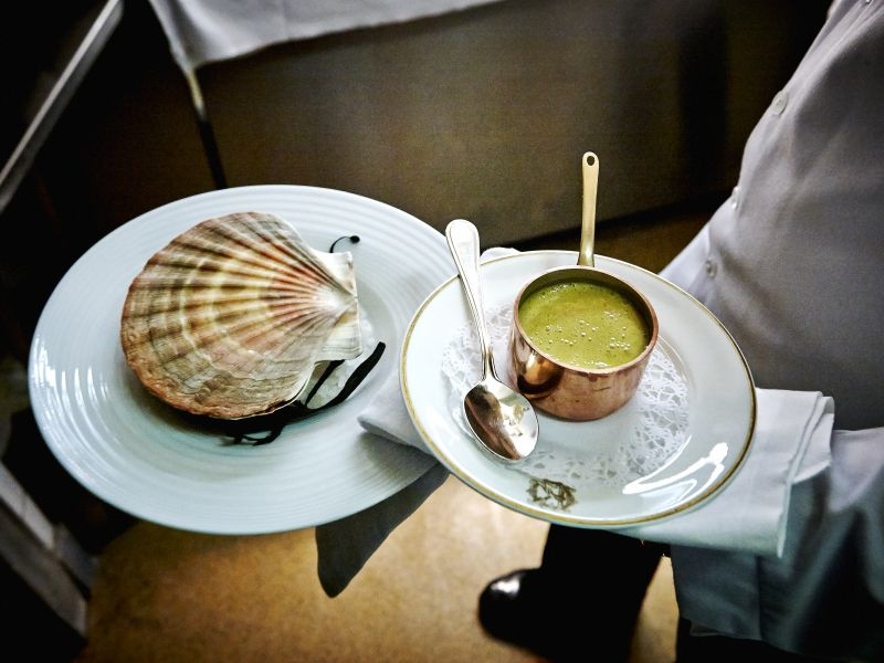 A server carries a plate with a large clam shell concealing a dish, and another with a small copper saucepot and a serving spoon