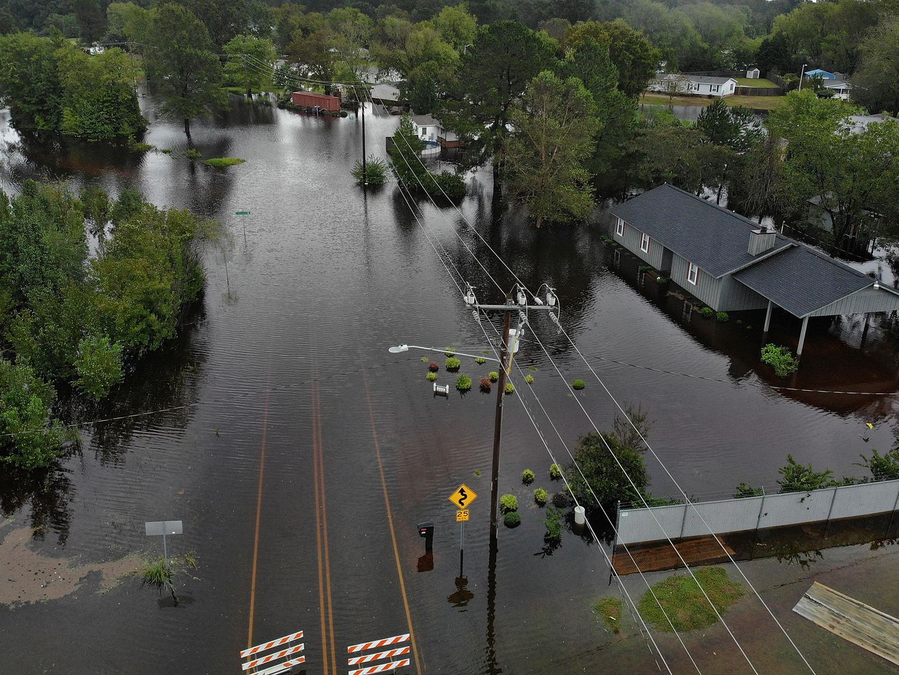 Flood waters from Hurricane Florence surround a house and flow along the street on September 16, 2018 in Fayetteville, North Carolina. Rain continues to inundate the region causing concern for large scale flooding after Hurricane Florence hit the North Carolina and South Carolina area.
