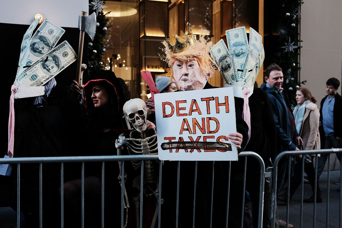 """A protestor wearing a Donald Trump paper mâché head stands in front of a barricade and holds a sign that reads, """"Death and taxes."""""""