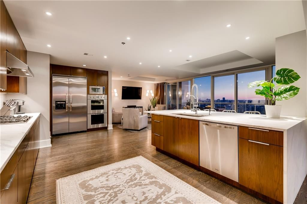 A white and wood kitchen in a huge condo with a skyline beyond.
