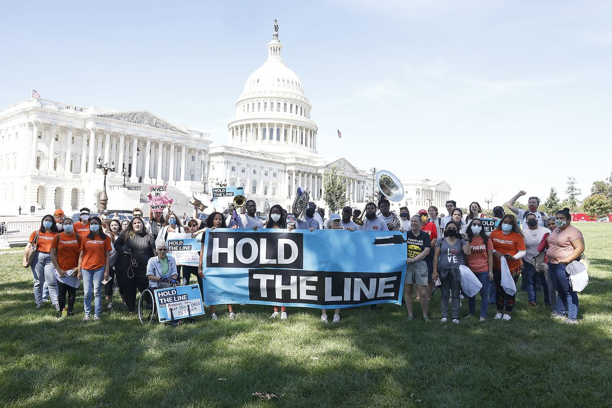 """Demonstrators stand on the lawn in front of the US Capitol holding a banner that reads """"hold the line."""""""