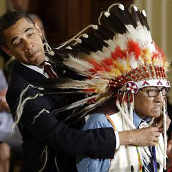 Obama reaches around the headdress of Native American historian Joe Medicine Crow to bestow on him a Medal of Freedom, the nation's highest civilian honor.