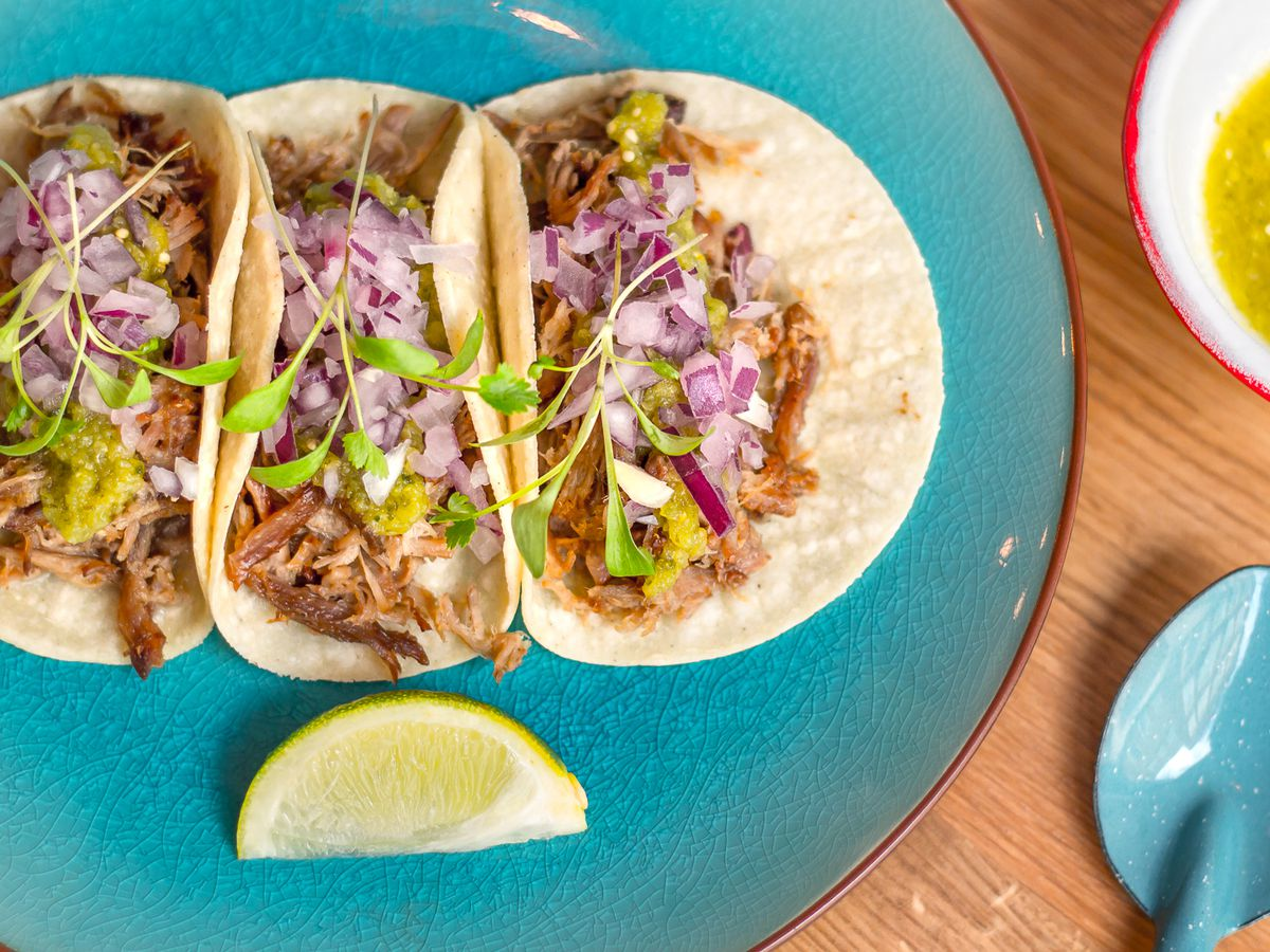 A plate of tacos on a blue plate with a lime wedge